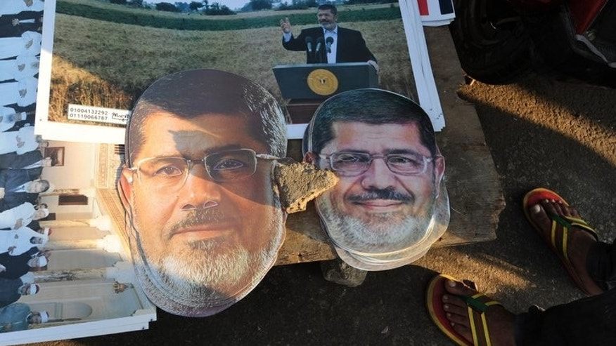 Masks of deposed president Mohamed Morsi are displayed as his supporters continue to hold a sit-in outside Rabaa al-Adawiya mosque in Cairo on July 25, 2013. A top Egyptian court has ordered that ousted president Mohamed Morsi be detained for questioning over suspected collaboration with Palestinian militant group Hamas, official MENA news agency reported Friday.