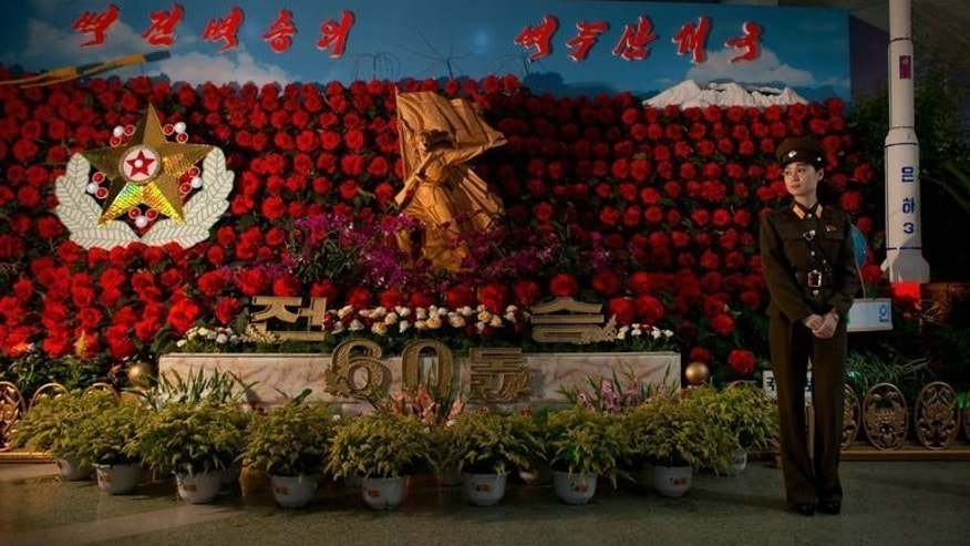 A North Korean soldier stands in front of a 'Kimilsungia' flower display at a flower festival in Pyongyang on July 26, 2013. It's a long way from your average flower show, with mock missiles bristling behind the begonias, and garden gnome-sized troops lobbing grenades over a bed of orchids. But then, as the staff in the hall in Pyongyang are quick to point out, these are far from average flowers.