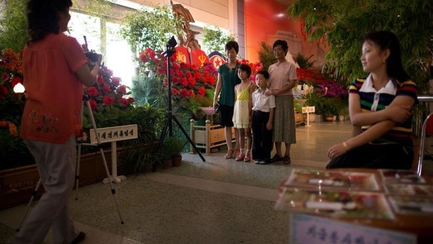 A North Korean family (C) have their photo taken as they visit a 'Kimilsungia' flower festival in Pyongyang on July 26, 2013.