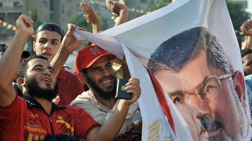 Supporters of deposed Egyptian president Mohamed Morsi hold up his portrait and shout slogans during a sit in outside Cairo's Rabaa al-Adawiya mosque on July 24, 2013. The Islamist Hamas rulers of the Gaza Strip slammed Egypt on Friday after a Cairo court ordered Morsi be detained for questioning over suspected collaboration with the Palestinian militant group.