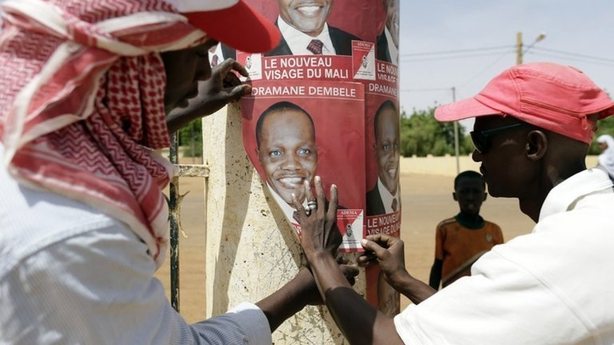 Supporters of Mali election candidate Dramane Dembele stick up posters on July 25, 2013 in Gao. Gao will join the rest of the country in electing a president on Sunday, and it is in northern Mali's largest city that the new head of state will have perhaps the heaviest workload.