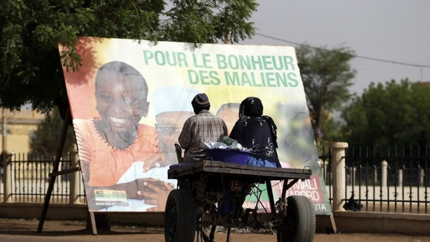 People pass by an electoral poster for Mali leader and presidential candidate Ibrahim Boubacar Keita on July 25, 2013 in Gao. Gao will join the rest of the country in electing a president on Sunday, and it is in northern Mali's largest city that the new head of state will have perhaps the heaviest workload.