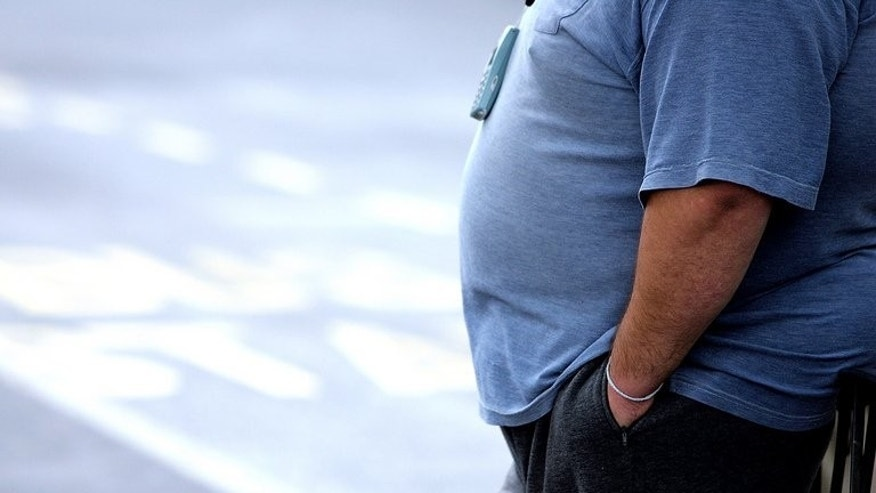 This file illustration photo shows an overweight man standing at a bus stop. An obese South African man has been told he is too fat to live in New Zealand despite shedding 30 kilograms since he moved to the country six years ago.