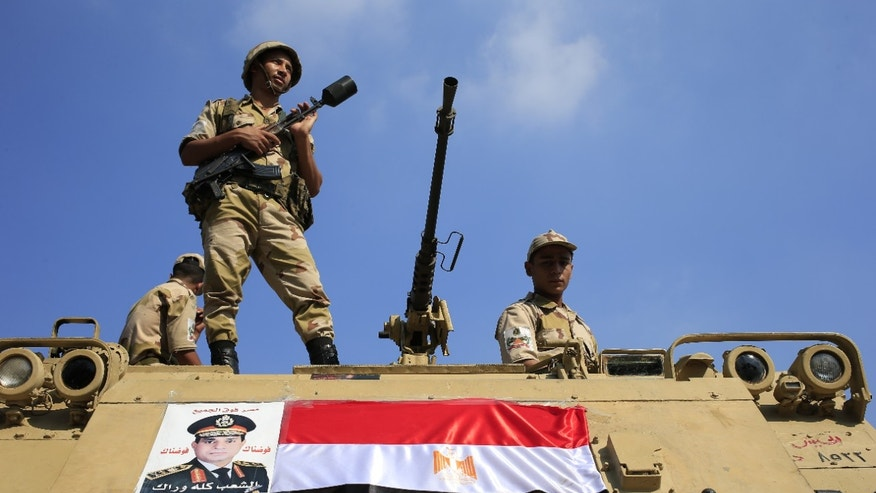 July 26, 2013: Egyptian soldiers stand guard atop an armored personnel vehicle on a bridge that leads to Tahrir Square in Cairo, Egypt.