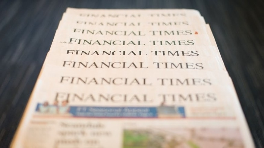 Copies of Pearson's Financial Times newspaper for December 11 last year. British publisher Pearson fell into a first-half net loss on the back of restructuring costs, the group said on Friday, but better-than-expected revenues sent its share price surging.