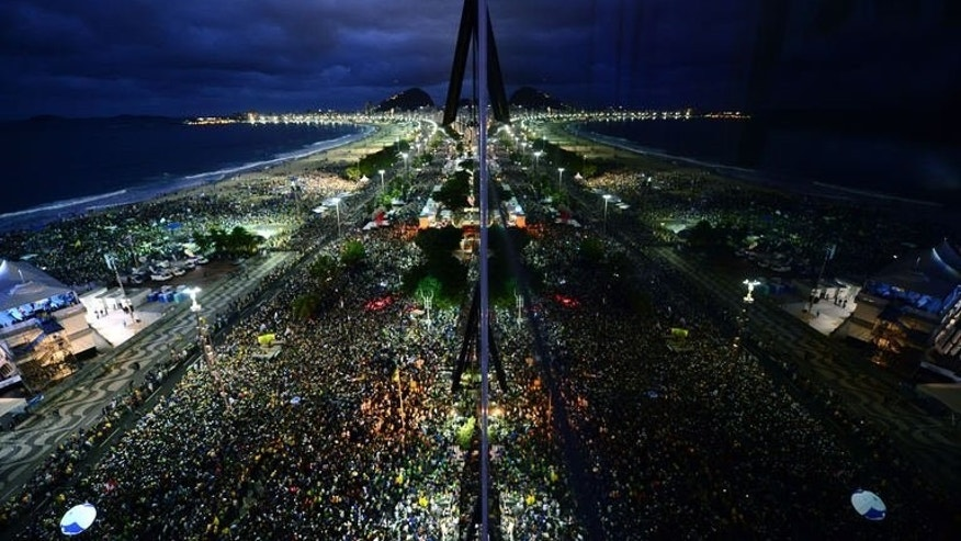 Thousands of young people gather at Rio de Janeiro's Copacabana beachfront on July 25, 2013 for the welcoming of Pope Francis for World Youth Day. The pope showed that his message of renewed faith in Jesus Christ can compete with the Rolling Stones and their Sympathy for the Devil.