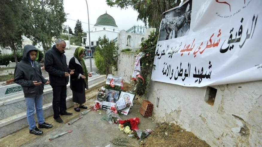 A Tunisian family prays at the grave of assassinated opposition leader Chokri Belaid on February 10, 2013 in Tunis. Assassinated opposition MP Mohamed Brahmi will be buried on Saturday next to Belaid, who was killed six months ago, Brahmi's wife said.