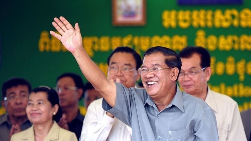 Cambodian Prime Minister Hun Sen (C) waving to onlookers during a ceremony in Takeo province on June 18, 2013. Cambodia's long-ruling party faces a rare leadership dilemma -- how do you replace a strongman premier who has run the country almost single-handedly for decades? Well, maybe with his son.