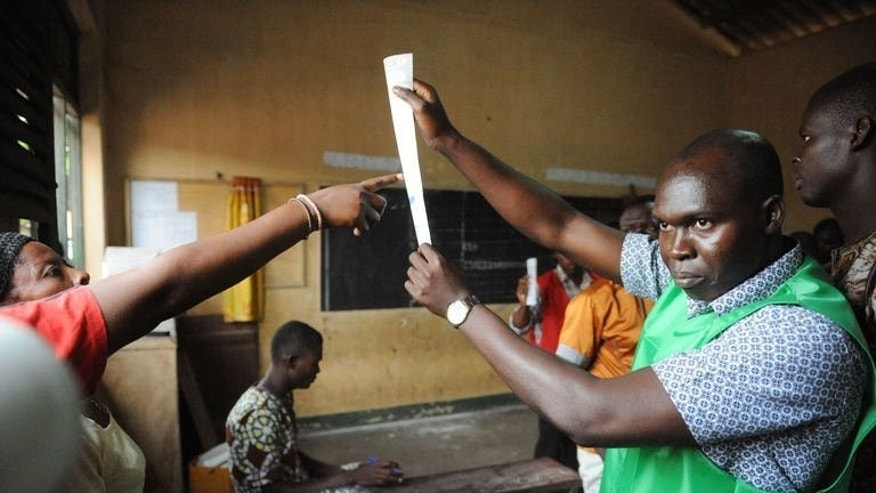 A member of Togo's Independent National Electoral Commission (CENI) displays an invalid vote on July 25, 2013 in Lome. The country was tallying votes after long-delayed parliamentary elections that were mainly peaceful and with the opposition seeking to weaken the ruling family's decades-long grip on power.