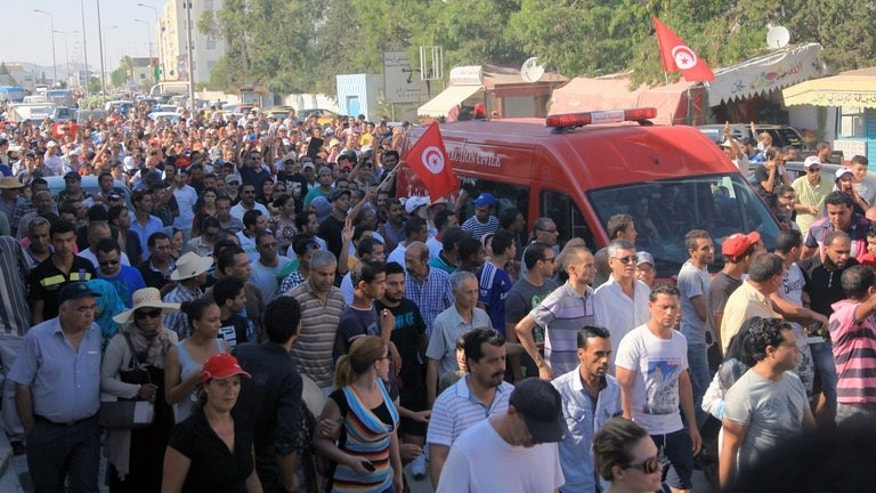 An ambulance, carrying the body of Tunisian opposition politician Mohamed Brahmi, drives to the Charles Nicile Hospital in Tunis after Brahmi was gunned down in front of his home on July 25, 2013. Tunisia faced a general strike on Friday as the country was plunged into crisis after the shooting, an assassination that brought thousands onto the streets.