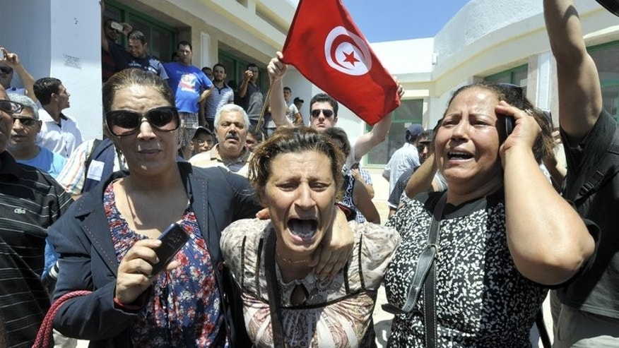 Women react outside a hospital after the killing of opposition politician Mohamed Brahmi on July 25, 2013 in Ariana, outside Tunis. Tunisia faced a general strike on Friday as the country was plunged into crisis after gunmen shot Brahmi dead, an assassination that brought thousands onto the streets