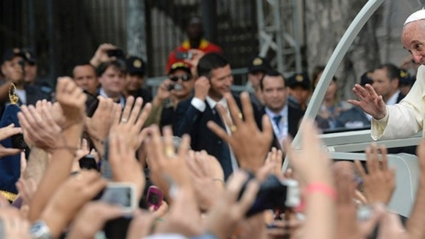 Pope Francis greets people from his popemobile as he arrives to Sao Joaquim square in Rio de Janeiro, Brazil, Friday, July 26, 2013. Pope Francis is on the fifth day of his trip to Brazil where he will attend the 2013 World Youth Day in Rio. (AP Photo/Luca Zennaro, Pool)