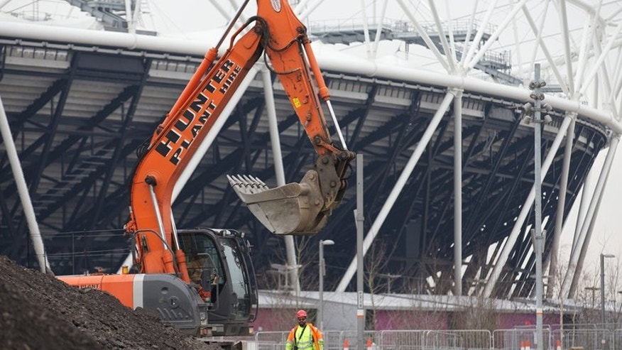 A digger is pictured in front of the London 2012 Olympic Stadium in east London, on January 25, 2013. A year after hosting the Olympics, London is trumpeting the economic benefits of the Games. But residents living near the Olympic Park are still waiting for the promised benefits as rents soar.