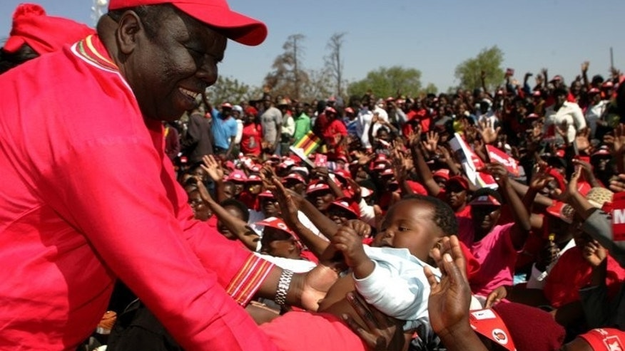 Zimbabwe Prime Minister Morgan Tsvangirai holds a baby during an election campaign rally in Gweru on July 21, 2013. Tsvangirai has warned that next week's election is strongly at risk of being rigged, and condemned the African Union's upbeat assessment of the poll preparations.