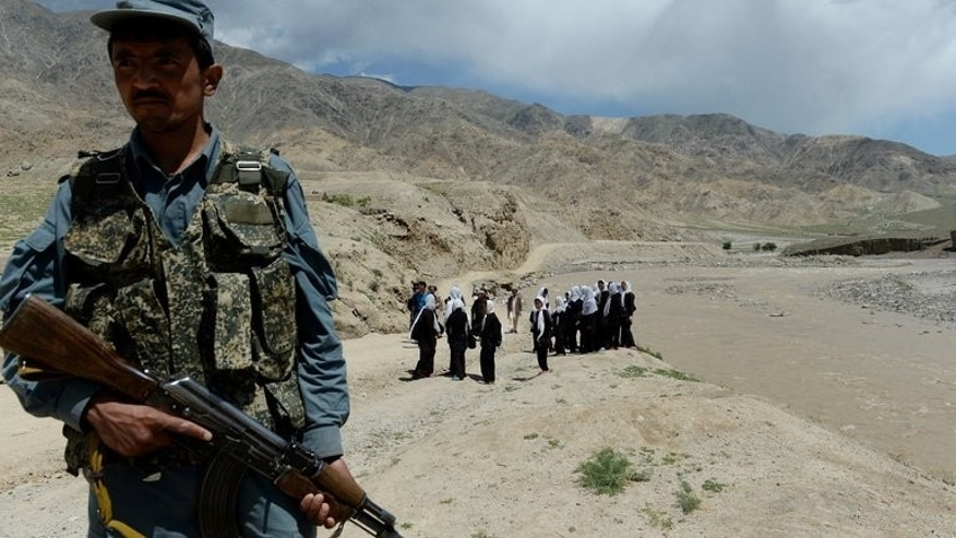 A policeman stands guard as schoolgirls wait for a bus in Qara Zaghan village in Baghlan province. Two Afghan civilians were killed and several injured following two failed assassination attempts by the Taliban which targeted a provincial governor and a police chief, officials said Saturday.