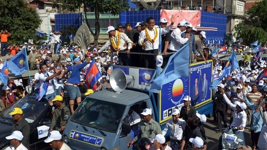 Sam Rainsy (center right) greets supporters during a campaign rally in Phnom Penh on Friday. Rainsy says his Cambodian National Rescue Party (CNRP) has uncovered irregularities such as tens of thousands of duplicated voter names that would allow some people to cast ballots twice in Sunday's polls.