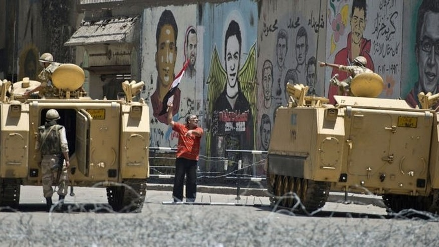 A man waves his national flag next to soldiers in their armoured vehicles as he walks towards Cairo's Tahrir square on July 26, 2013. Egyptian police shot dead 23 supporters of Egypt's ousted president Mohamed Morsi and wounded hundreds more in Cairo early on Saturday, a Muslim Brotherhood leader told AFP.
