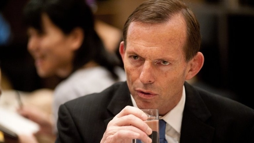 "Australian opposition leader Tony Abbott, pictured in Beijing, on July 24, 2012. Nations's first female leader Julia Gillard has spoken out against the ""glossed over"" sexism of her tenure. Gillard gave the example of Abbott once campaigning in front of placards that said ""Ditch the Witch."""