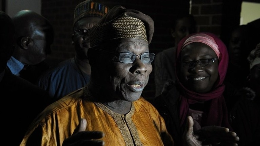 Former Nigerian president Olusegun Obasanjo (C) addresses the media upon arrival in Harare, on July 27, 2013. Obasanjo is to lead a team of 60 African Union monitors for Zimbabwe's July 31 election.