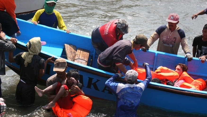Rescuers assist asylum-seekers who survived the sinking of a boat heading for Australia, on July 24, 2013. Police detained four people allegedly involved in arranging the boat which sank, killing at least 15 people.