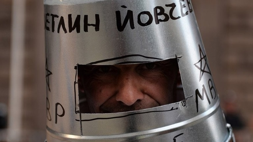"A protester wears a bucket on his head during an anti-government demonstration in Sofia on Friday. Almost three quarters of Bulgarians consider their country ""intolerable"", according to a new survey released Saturday by the Open Society Institute, following weeks of protest against the government and a worsening economy."