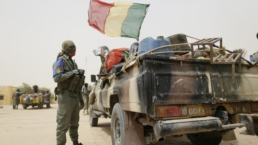 """Malian soldiers patrol on a road between Gao and Kidal on July 26, 2013 in northern Mali. Millions of Malians are expected to vote Sunday in """"imperfect"""" elections they hope will usher in a new dawn of peace and stability in a country torn apart by an 18-month political crisis and armed conflict."""