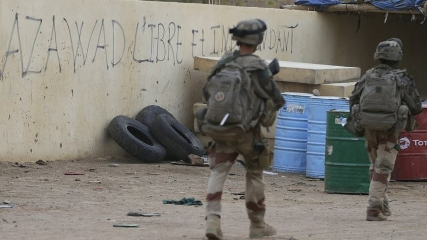 "French soldiers walk past a graffito that reads ""Azawad free and independent"" as they patrol on July 27, in Kidal, Mali. On the eve of Mali's watershed presidential election, the authorities in the rebel bastion of Kidal were confident Saturday of well-run polls, although they were under no illusions about getting a big turn-out."