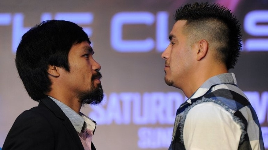 Philippine boxing icon Manny Pacquiao (L) and Brendon Rios of the US go face-to-face during a pre-fight press conference in Macau on July 27, 2013. Pacquiao insists he is as fit as ever and has ignored calls from friends, family and media commentators, fearful for his health, to call it a day.