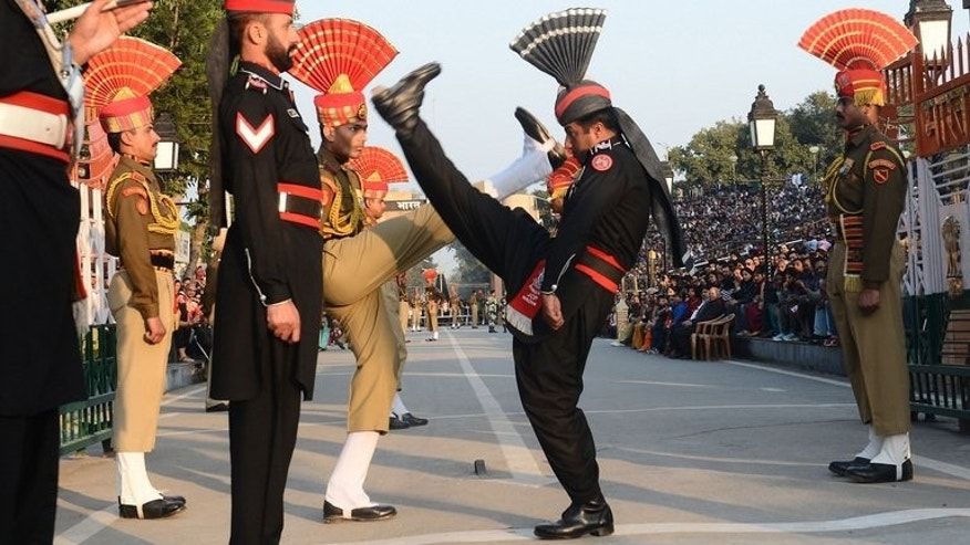 "Pakistani (in black) and Indian border troops perform the 'flag off' ceremony at Wagah border post. Indian troops shot and killed one Pakistani soldier and injured another in an ""unprovoked"" attack across the countries' disputed border in Kashmir, Pakistan's army said Saturday."