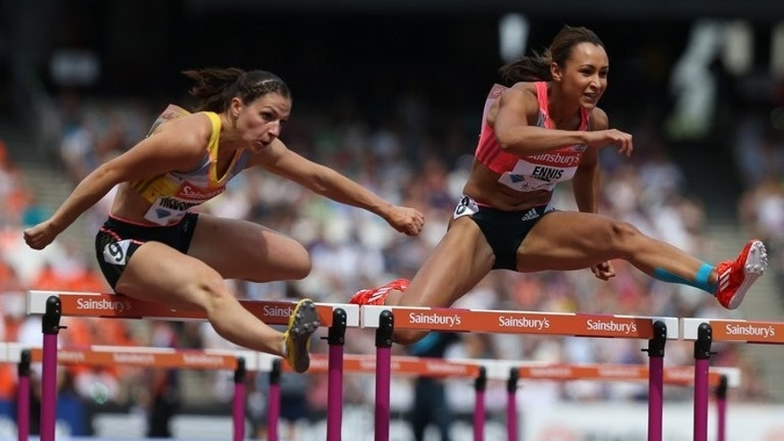 Jessica Ennis-Hill (right) of Great Britain takes the lead against Nadine Hilderbrand of Germany in the womens 100 metres hurdles event during the London Anniversary Games International Association of Athletics Federations (IAAF) Diamond League International Athletics championships at the Olympic Stadium in London on July 27, 2013.