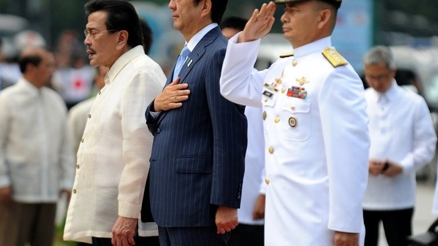 Japan's Prime Minister Shinzo Abe (C) stands next to current Manila mayor and former Philippine president Joseph Estrada (L) during a wreath laying ceremony at the monument of Philippine national hero Jose Rizal, in Manila, on July 27, 2013. Abe is in Manila for a two-day visit focusing on defence cooperation amid territorial disputes with China.