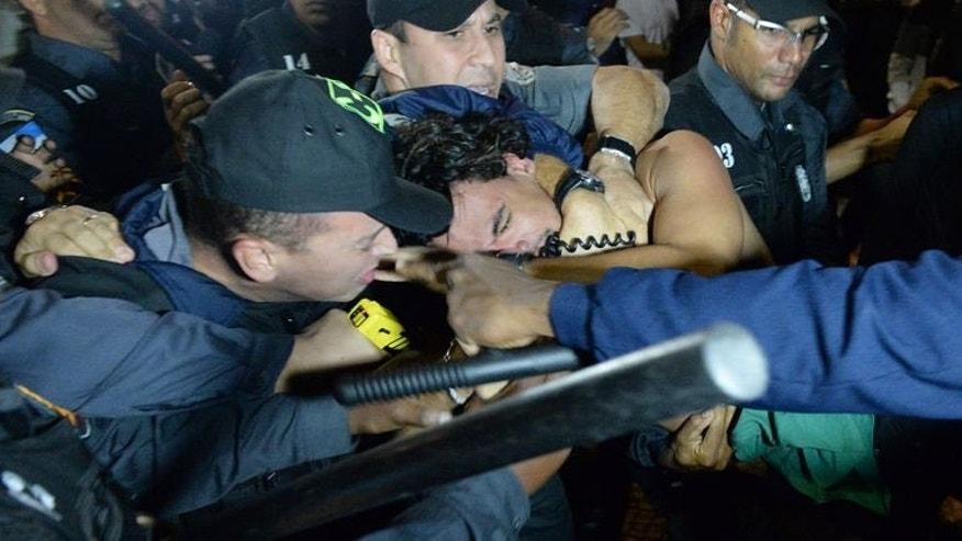 Police officers use a Taser gun on a demonstrator during a protest against corruption in Rio de Janeiro. The protest took place near where visiting Pope Francis was wrapping up a massive ceremony with hundreds of thousands of young Catholics at Copacabana beach, on July 26, 2013.