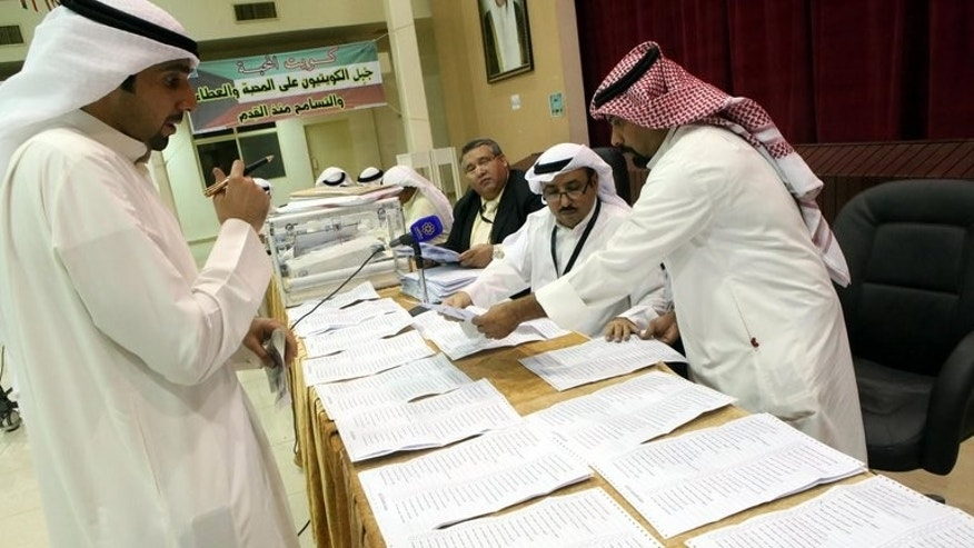 Judges and their aides count the ballots at a polling station in Kuwait City on July 27, 2013. Kuwait's Shiite minority lost more than half of their seats and liberals made slight gains in the Gulf state's second polls in eight months.