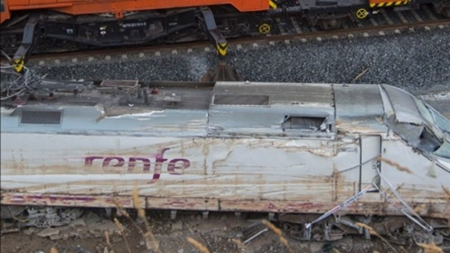 A passenger train passes the wreckage of a train in Santiago de Compostela, Spain, Saturday July 27, 2013. Spain's interior minister Jorge Fernandez Diaz says the driver whose speeding train crashed, killing 78 people, is now being held on suspicion of negligent homicide. The Spanish train  derailed at high speed Wednesday killing 78 and injuring dozens more. (AP Photo/Lalo R. Villar)