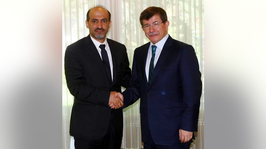 "Ahmad Jarba (left) with Turkish Foreign Minister Ahmet Davutoglu in Istanbul on July 9. Jarba has asked France and the United States to supply arms and called on the UN Security Council to increase ""pressure"" on Bashar al-Assad."