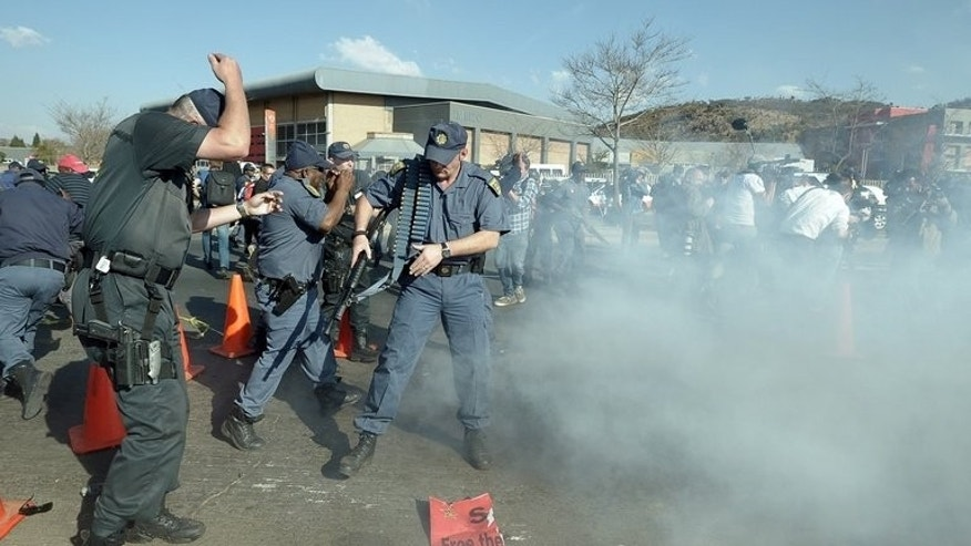 South African Police react after firing rubber bullets at protesters rallying against President Barack Obama's visit to South Africa, in Soweto on June 29, 2013. Almost 1,500 of South Africa's police officers have themselves committed crimes in a nation where security forces are notorious for brutality and corruption, according to an audit released Sunday.