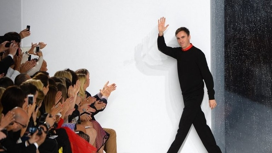 "Belgian fashion designer Raf Simons for Christian Dior acknowledges the audience at the end of the show of his collection, entitled ""Croisiere 2014,"" (Cruise), in Monaco, on May 18, 2013. The designer, who notably put models from all corners of the globe on the catwalk, says his latest collection shows Dior ""not just being about Paris and France, but about the rest of the world"" too."
