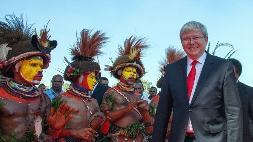 "Huli wigmen greet Australian Prime Minister Kevin Rudd as he arrives at the parliament house in Port Moresby, on July 15, 2013. Rudd on Sunday said he made ""absolutely no apology"" for his hardline new policy on asylum-seekers under which they are sent to Papua New Guinea."
