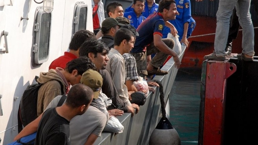 A group of asylum seekers are seen aboard an Indonesian maritime police boat in the port of Banten, western Java island, on October 9, 2012, three days after their boat was badly damaged after hitting the reef in rough seas. They were intercepted as they tried to reach Australia's Christmas Island.