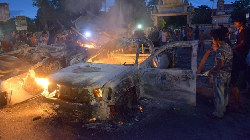 A police car burns amid protests during the general election in Phnom Penh, on Sunday. Protests broke out at one polling station in the capital Phnom Penh where a crowd destroyed two police cars, military police spokesman Kheng Tito said, as anger erupted over names missing from the voter list.