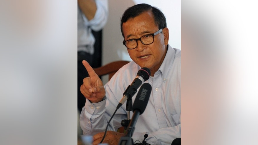 "Sam Rainsy, leader of the opposition Cambodia National Rescue Party (CNRP), speaks to the media during a press conference in Phnom Penh, on July 27, 2013. Rainsy denounced signs of voter fraud on the eve of elections and labelled Prime Minister Hun Sen a ""coward"" for not allowing him to participate."