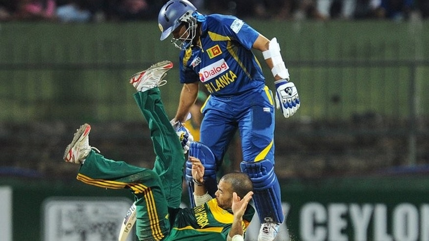Sri Lankan batsman Tillakaratne Dilshan (R) collides with South African cricketer Jean-Paul Duminy (L) during the fourth One Day International (ODI) cricket match between Sri Lanka and South Africa in Pallekele on July 28, 2013.
