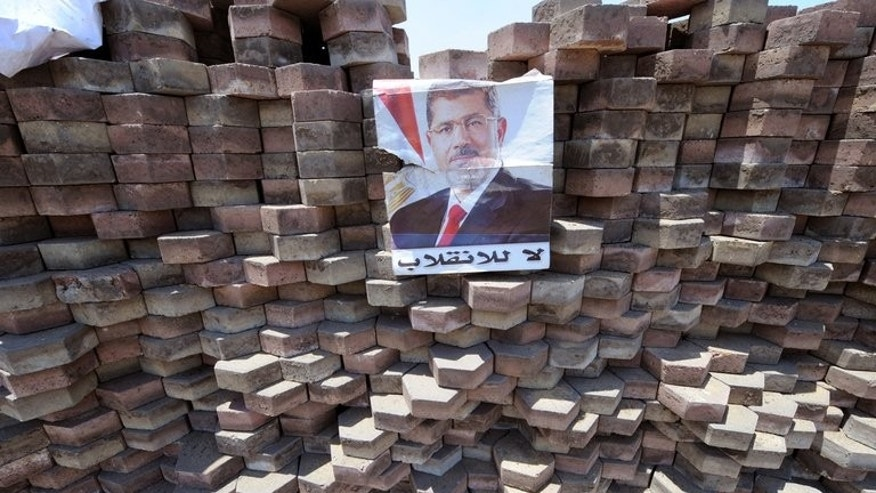 "A poster of deposed president Mohamed Morsi with the slogan ""No to the overthrow"", is displayed on a makeshift barricade on Nasr City's main street, a district of eastern Cairo, on July 28, 2013. EU foreign policy chief Catherine Ashton flew into Egypt for talks Monday as international pressure increased on the new regime over the weekend's violence, which claimed more than 80 lives."