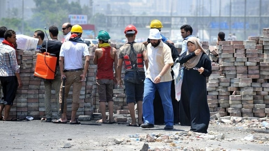 A couple walk past Muslim Brotherhood members at a makeshift barricade in Nasr City, eastern Cairo, on Sunday. EU foreign policy chief Catherine Ashton flew into Egypt for talks Monday as international pressure increased on the new regime over the weekend's violence, which claimed more than 80 lives.
