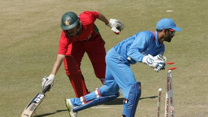 Zimbabwe's batsman Sean Williams (left) is run-out by Indian wicket keeper Dinesh Karthik at Harare Sports Club on July 28, 2013. India moved closer to a straightforward one-day series victory over Zimbabwe after bowling the hosts out for 183 in the third match on Sunday.
