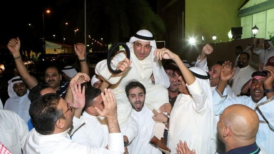 Poll candidate Jamal al-Omar (C) celebrates with supporters following parliamentary elections, in Kuwait City, on July 28, 2013. The Kuwaiti government on Sunday submitted its resignation to the oil--rich Gulf state's ruling emir in line with the constitution a day after parliamentary elections, an official statement said.