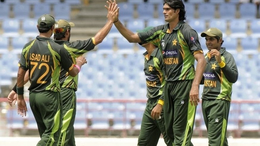 Pakistan bowler Mohammad Irfan (C) celebrates the dismissal of West Indies batsman Johnson Charles, caught Haris Sohail (R) during the 5th and final ODI West Indies v Pakistan on July 24, 2013. Pakistan defeated the West Indies by 11 runs to sweep the Twenty20 series 2-0 at Arnos Vale.
