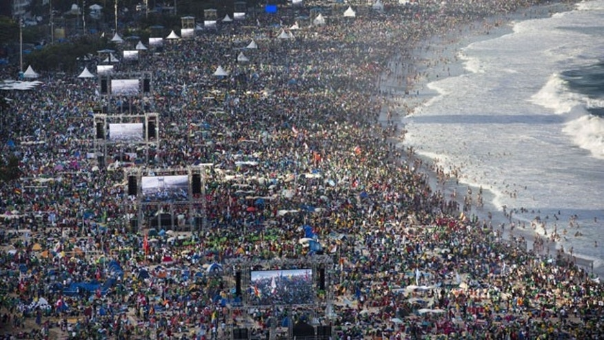 July 27, 2013: Pilgrims and residents gather on Copacabana beach before the arrival of Pope Francis for World Youth Day in Rio de Janeiro, Brazil. (AP Photo)