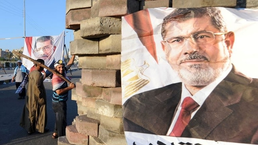 An image of deposed president Mohamed Morsi at a makeshift brick barricade erected along Nasr City's main street, a district of eastern Cairo, on July 28, 2013. They have seen dozens killed among their ranks and their prospects of success appear remote but supporters of Morsi have faith he will be reinstated.