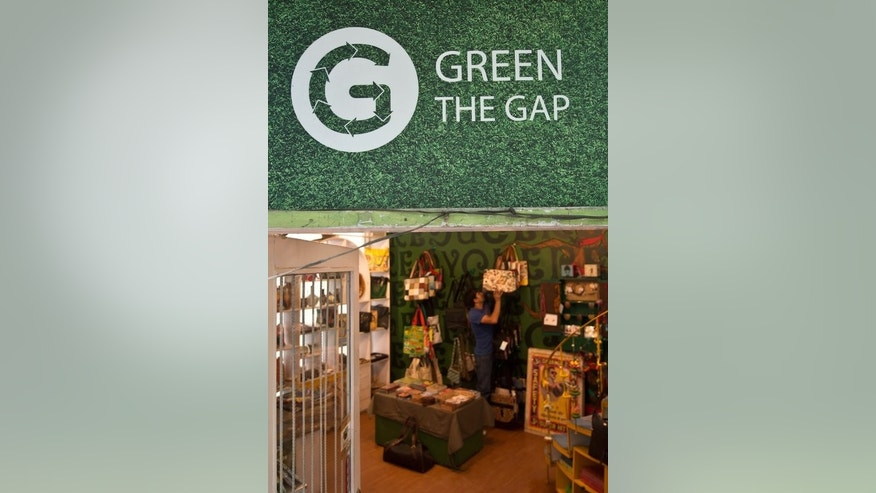 A sales-assistant arranges recycled goods at a Green The Gap store in New Delhi, on July 26, 2013. Green the Gap, an Indian recycling company which uses junk to create accessories is fighting a legal trademark suit launched by US clothing giant Gap Inc demanding that the firm change its name.